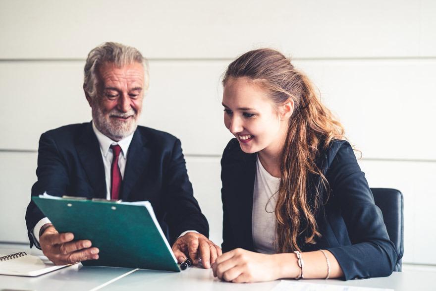 Geschäftsfrau mit Laptop im Gespräch mit einer Praktikantin