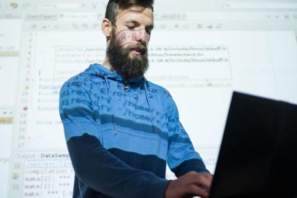 Ein Mann schaut in seinen Latop und tippt etwas ein, im Hintergrund wird sein Desktop, auf dem programmiersprache zu sehen ist, auf eine Wand und den Mann projeziert