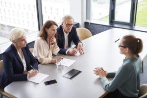 Eine junge Frau sitzt am Tisch gegenüber von drei Mitarbeitern, die sie prüfend anschauen und ihr zuhören
