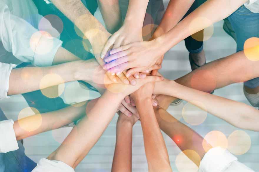 Aufeinander gelegte Hände als Symbol für Teamgeist.