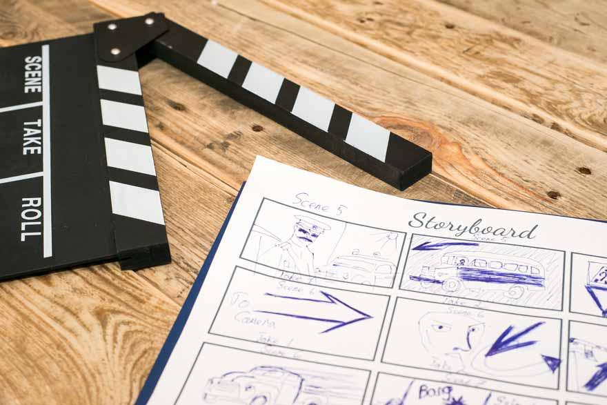 Das Storyboard und eine Filmklappe für ein Bewerbungsvideo liegen auf einem Holztisch.