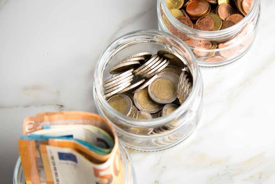 Drei mit Münzen und Scheinen gefüllte Geldgläser.