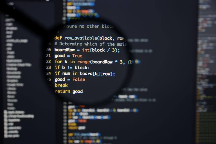 Eine Lupe vergrößert einen Ausschnitt von Codezeilen
