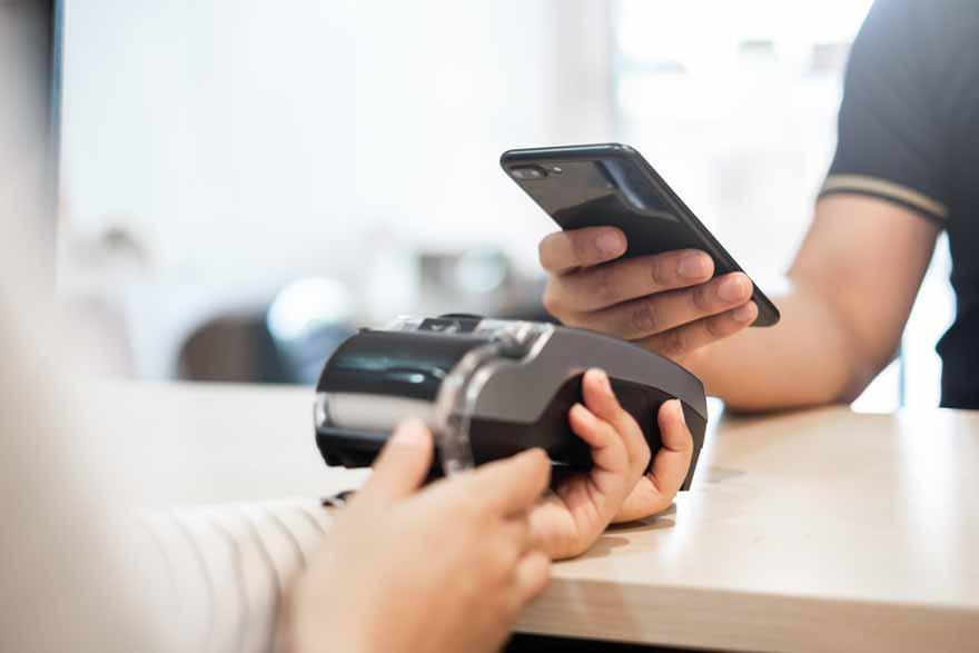 Ein Kunde der an einem NFC-Termminal mit seinem Smartphone bezahlt.NFC Terminal