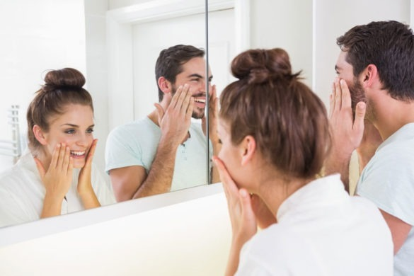 Junge Frau und junger Mann blicken nebeneinander in den Spiegel und betrachten sich selbst