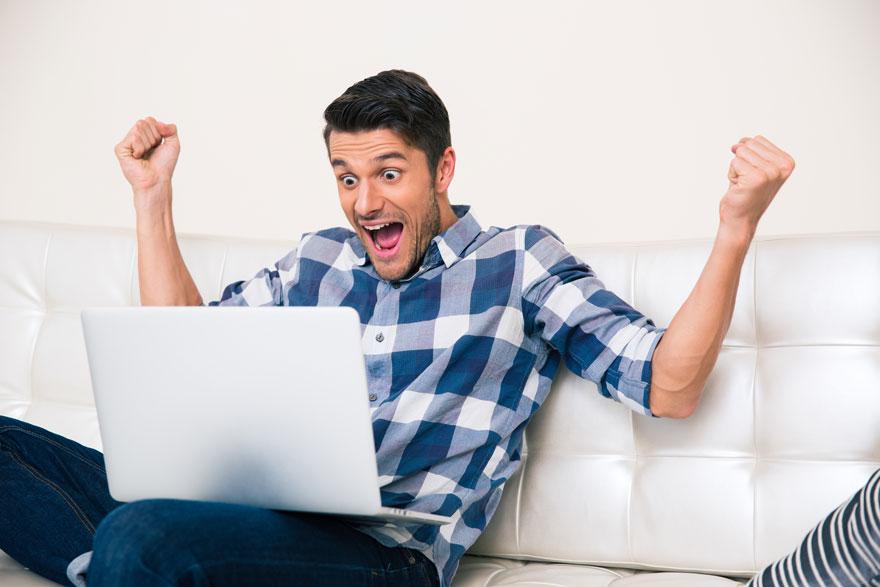 Mann mit blau weiß kariertem Hemd sitzt mit seinem Laptop auf dem Sofa und jubelt