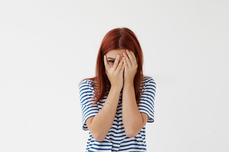 Schüchterne junge Frau mit roten Haaren und gestreiftem T-Shirt verdeckt ihr Gesicht mit den Händen und linst zwischen zwei Fingern hindurch