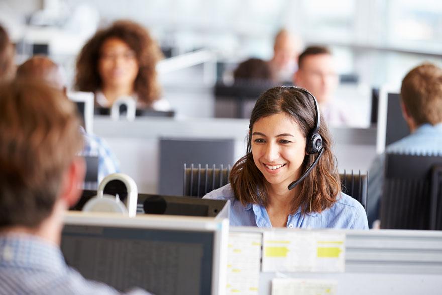 Junge Frau telefoniert glücklich umgeben von ihren Kollegen an ihrem Arbeitsplatz im Callcenter