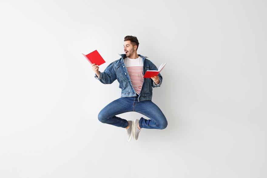 Junger Mann springt vor Freude in die Luft.