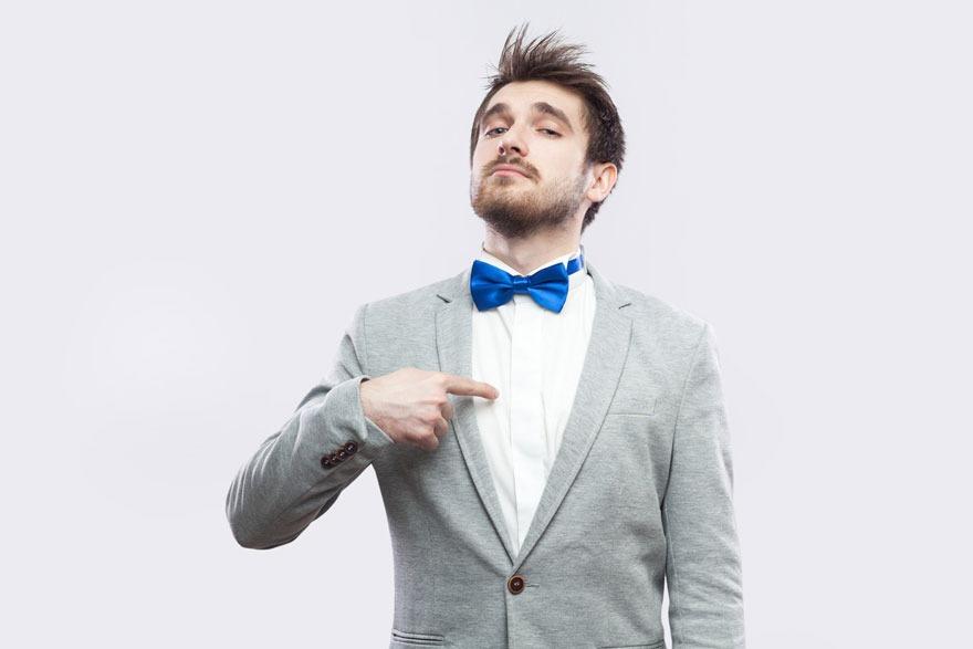 Junger Mann mit grauen Jacket und blauer Fliege reckt übertrieben selbstbewusst die Nase nach oben und zeigt mit dem Zeigefinger auf seine Brust