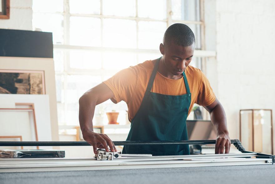 Junger Mitarbeiter arbeitet in seinem Handwerksbetrieb an der Herstellung eines Bilderrahmens