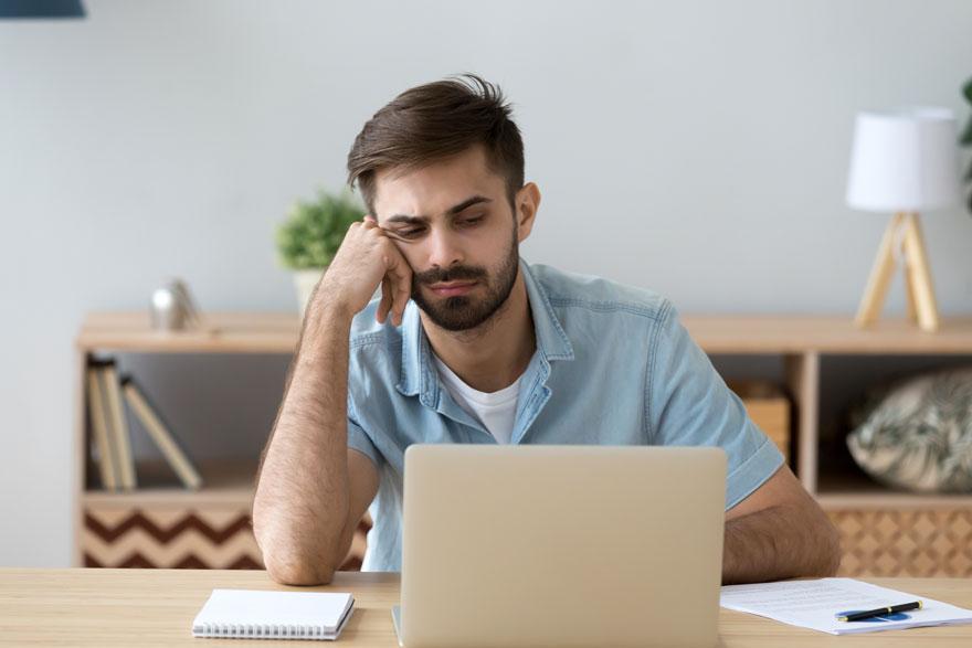 Ein junger, unmotivierter Mitarbeiter sitzt im Homeoffice lustlos vor seinem Laptop