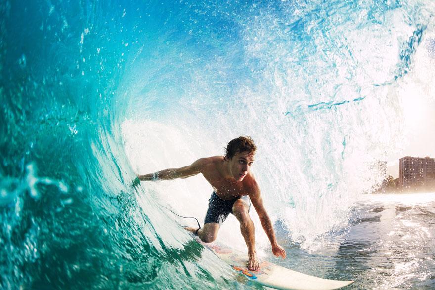 Junger Surferboy auf seinem Surfbrett in blauer Riesenwelle