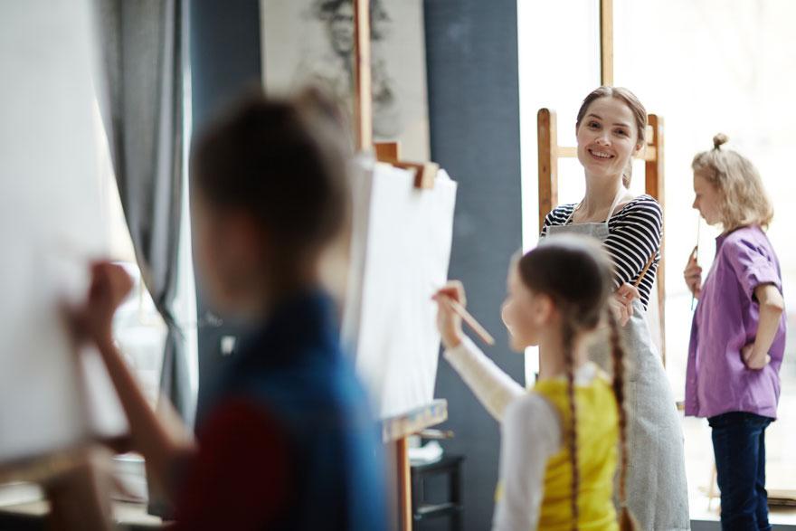 Junge Lehrerin mit drei Kindern vor Staffeleien