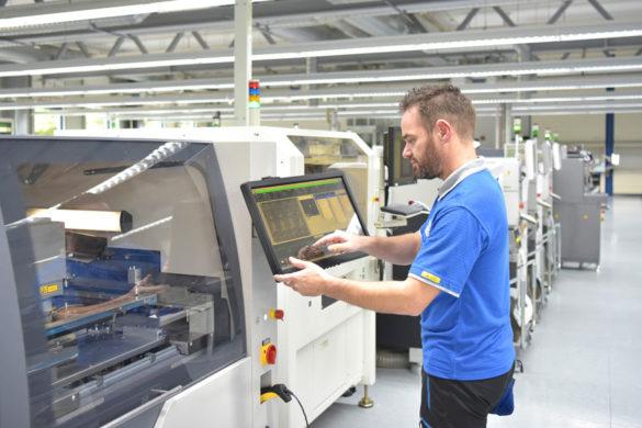 Produktionsmitarbeiter arbeitet an einer Maschine in einer Produktionsstraße.