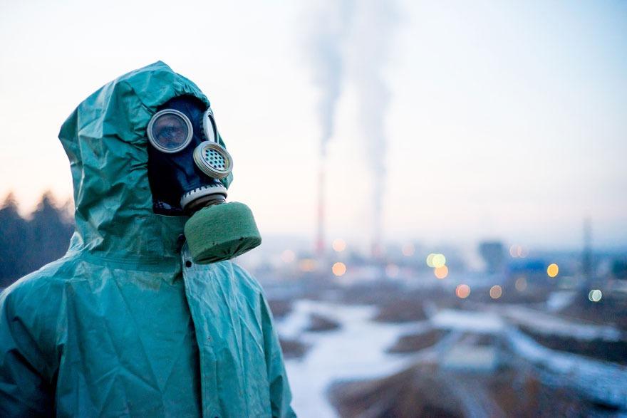 Person steht mit Gasmaske und Schutzanzug vor trister Landschaft