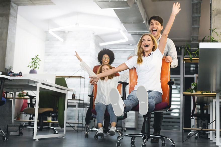 Junges Team veranstaltet voller Spaß ein Bürostuhlrennen im Büro