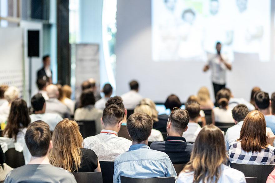 Männlicher Technology Evangelist versucht ein großes Auditorium durch seinen Vortrag zu begeistern