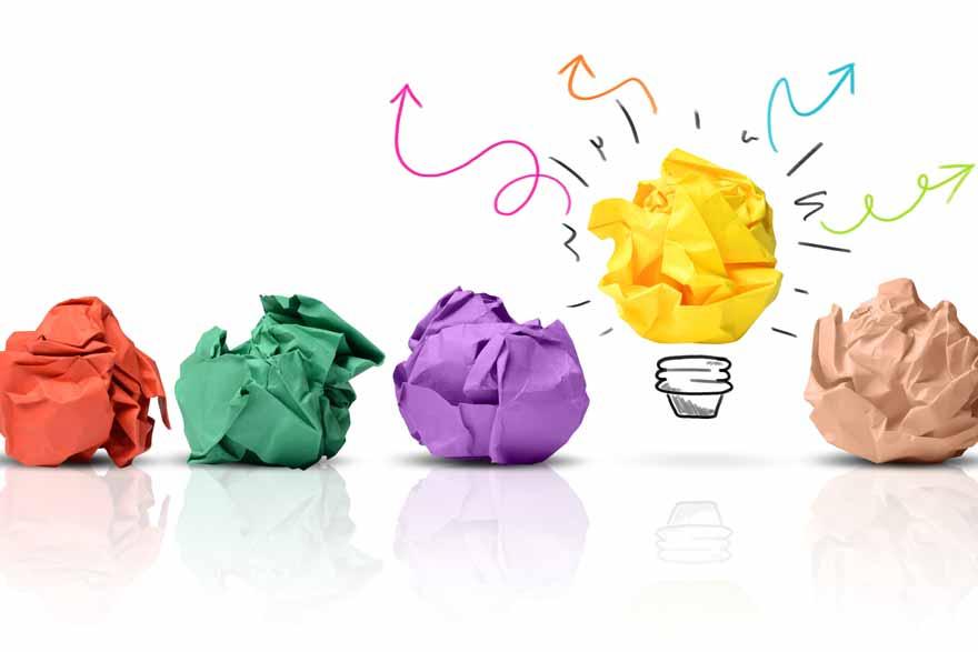 Verworfene Ideen neben einer sehr guten Idee dargestellt als zerknülltes Papier und Glühbirne.