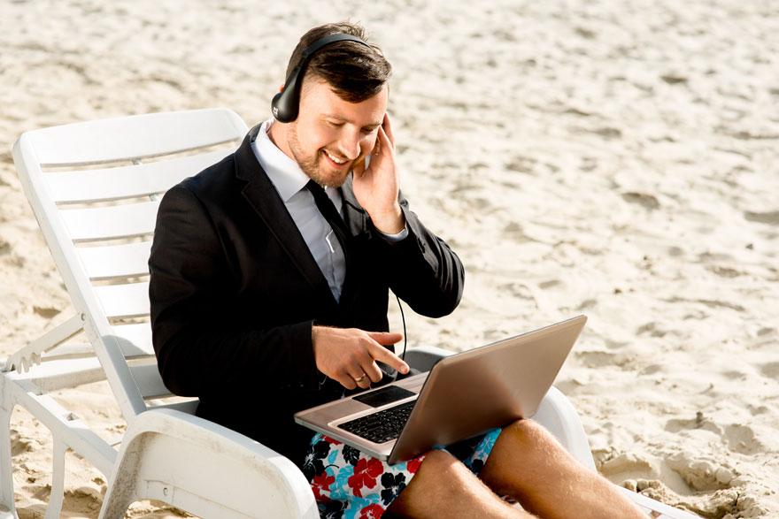 Bewerber sitzt mit Laptop in Hemd, Jacket und Badehose auf einer Liege am Strand zum Videointerview