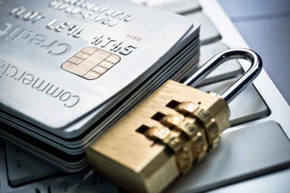 Ein Kreditkartenstapel neben einem Zahlenschloss auf einer Tastatur.