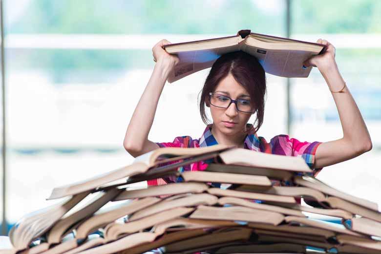 Junge Studentin steht überfordert vor einem Stapel Bücher und überlegt ihr Studium abzubrechen.