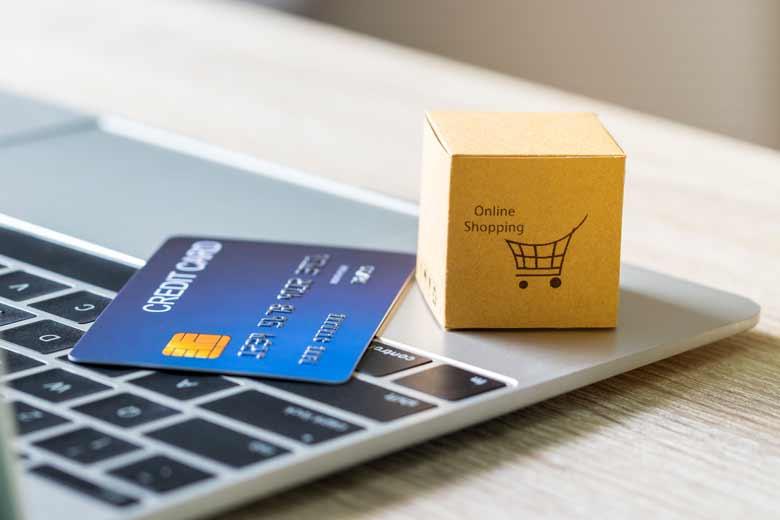 """Laptop auf dem eine Kreditkarte und Würfel liegt. auf dem Würfel steht """"Online Shopping"""" geschrieben."""""""