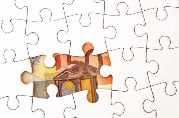Puzzle bei dem zwei Teile fehlen. An deren Stelle ragt ein 50 Euroschein hervor.