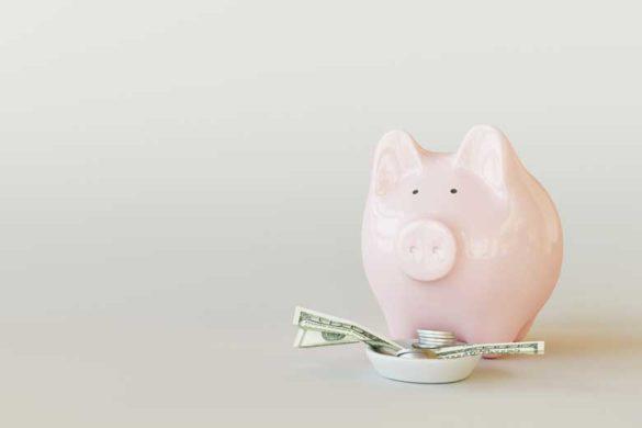 Sparschwein aus dem Geldscheine herausragen.