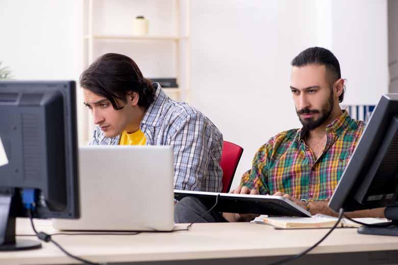 Zwei IT Spezialisten an ihrem Arbeitsplatz beim Coden.