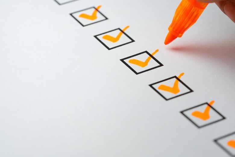 Checkliste mit orangenen Häckchen wird gerade abgehakt