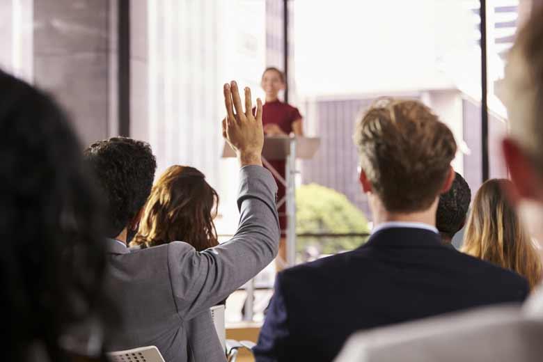 CEO hält Präsentation ein Mitarbeiter hebt die Hand.
