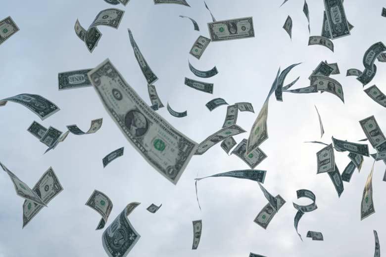 Eine Vielzahl Dollarscheine die vom Himmel regnen.