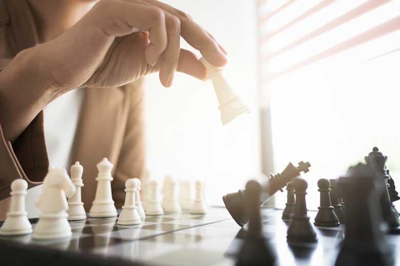 Eine Frau spielt Schach und wirft gerade eine schwarze Figur mit ihrer weißen Figur um.