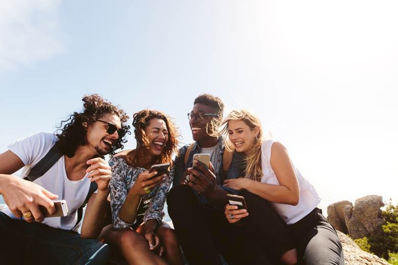 Eine Gruppe junger Leute mit ihren Smartphones im FOMO-Rausch