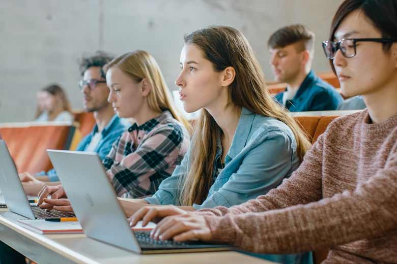 Eine Gruppe Studenten im Hörsaal folgt aufmerksam der Vorlesung.