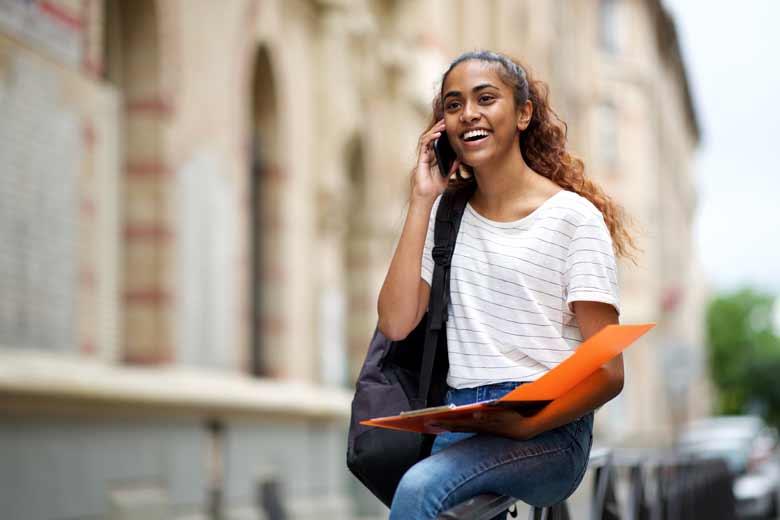 Eine junge Bewerberin erhält eine zusage am Telefon.