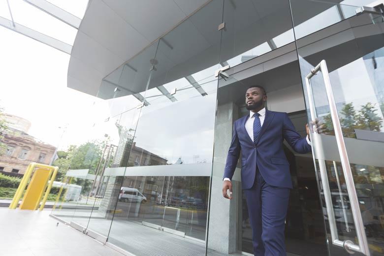 Junger Bewerber verlässt Bürogebäude nach Vorstellungsgespräch.