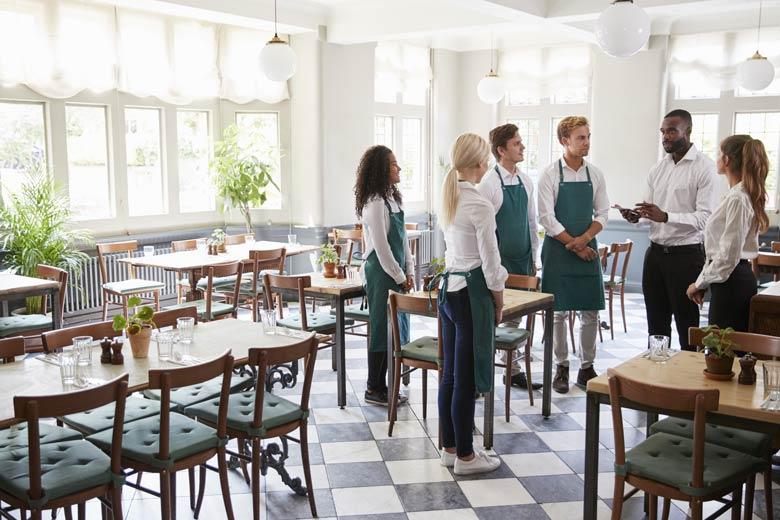 Mitarbeiter in einem Restaurant bekommen Anweisungen von ihrem Vorgesetzten.
