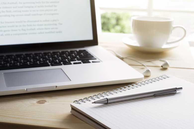 Notizblock mit Stift neben Laptop
