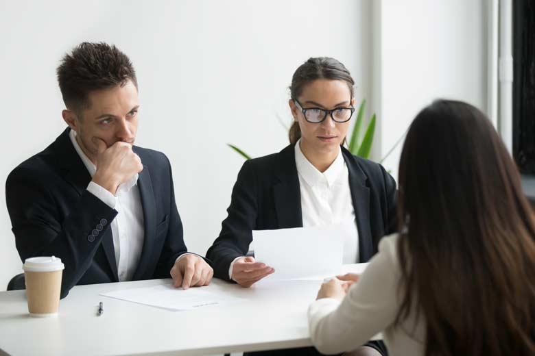 Personaler nehmen Bewerberin im Vorstellungsgespräch in die Mangel.