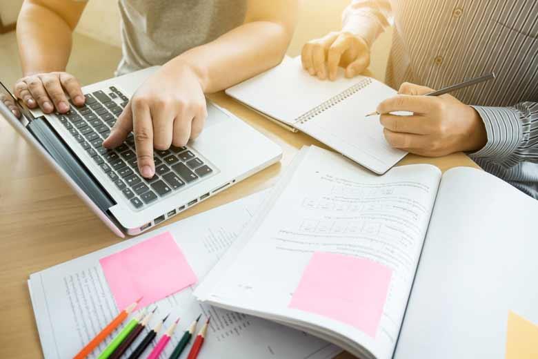 Studenten lernen gemeinsam mit dem Laptop und Stift und Papier.