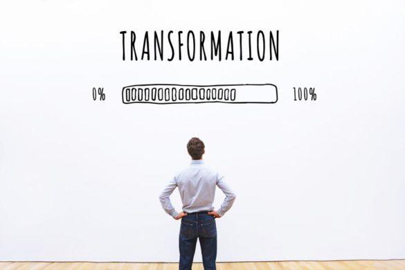 """Mann vor einer weißen Wand auf der Transformation steht. Darunter ein """"Ladebalken"""" der sich langsam füllt."""