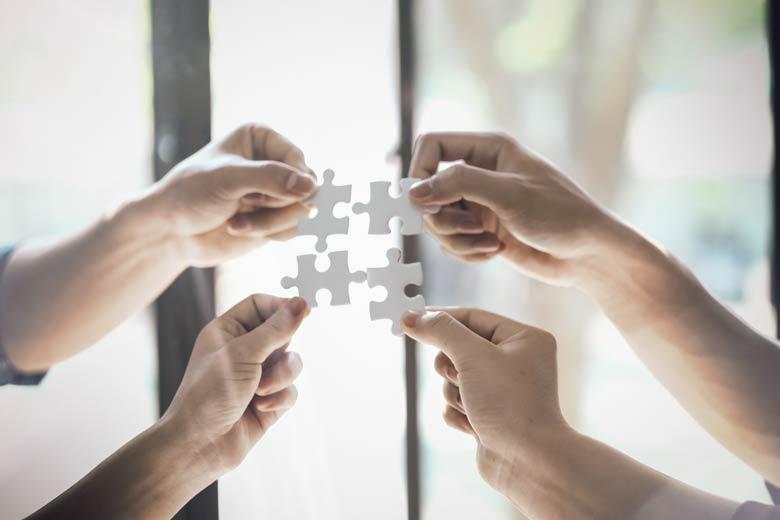 Vier Puzzleteile werden von vier Händen aneinander gehalten.