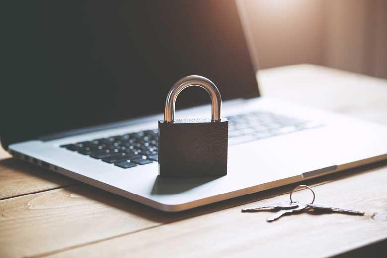 Ein Vorhängeschloss steht auf einem Laptop auf einem Schreibtisch