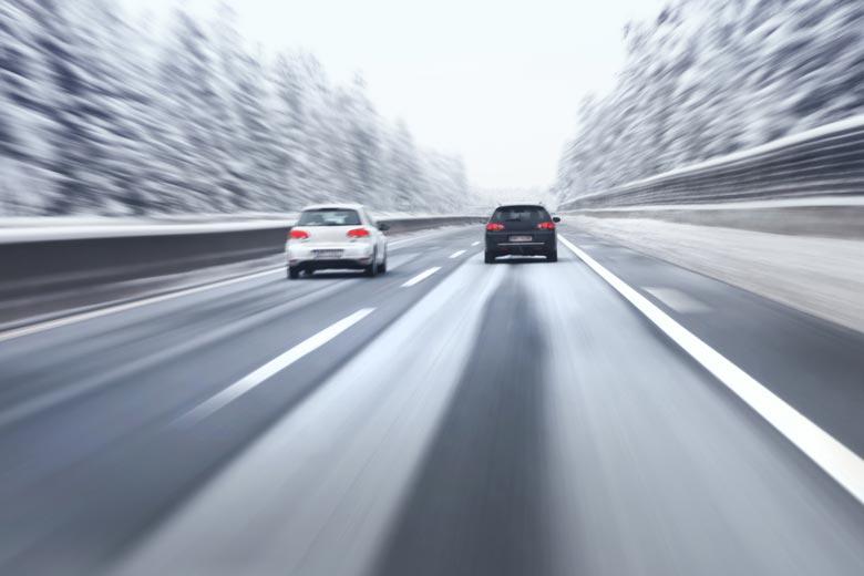 Ein weißer und ein schwarzer PKW auf einer verschneiten Fahrbahn