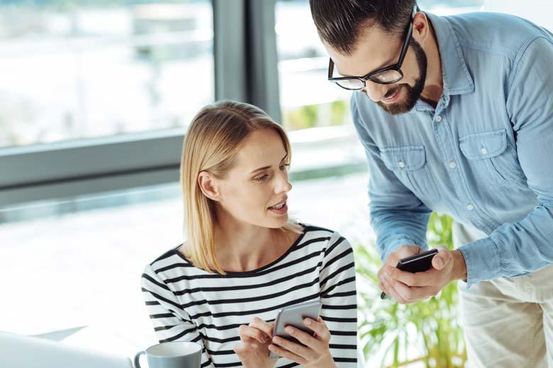 Arbeitskollegen zeigen sich gegenseitig witzige Emails auf dem Smartphone