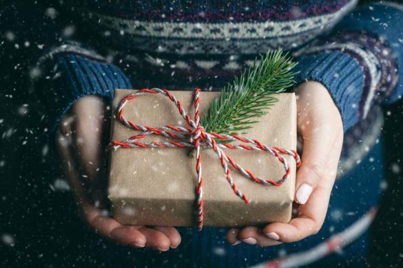Die Symbolik des Schenkens, zwei Hände halten ein Weihnachtsgeschenk