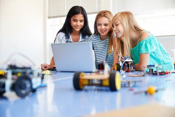Drei Schülerinnen programmieren einen Roboter