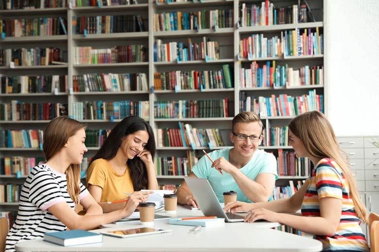 Eine Gruppe junger Studenten lernt gemeinsam in der Bibliothek